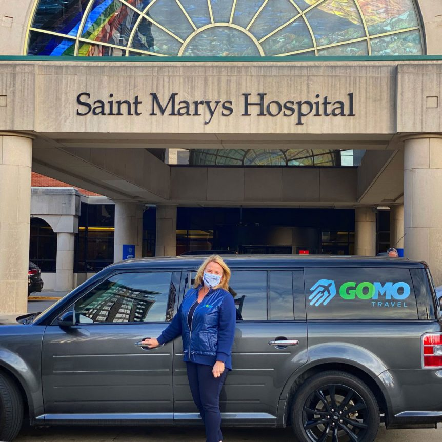 Kerri Johnson standing in front of Gomo Travel Luxury SUV and Saint Marys Hospital Building